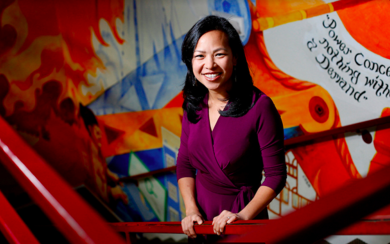 Vien Truong smiling in front of a red railing