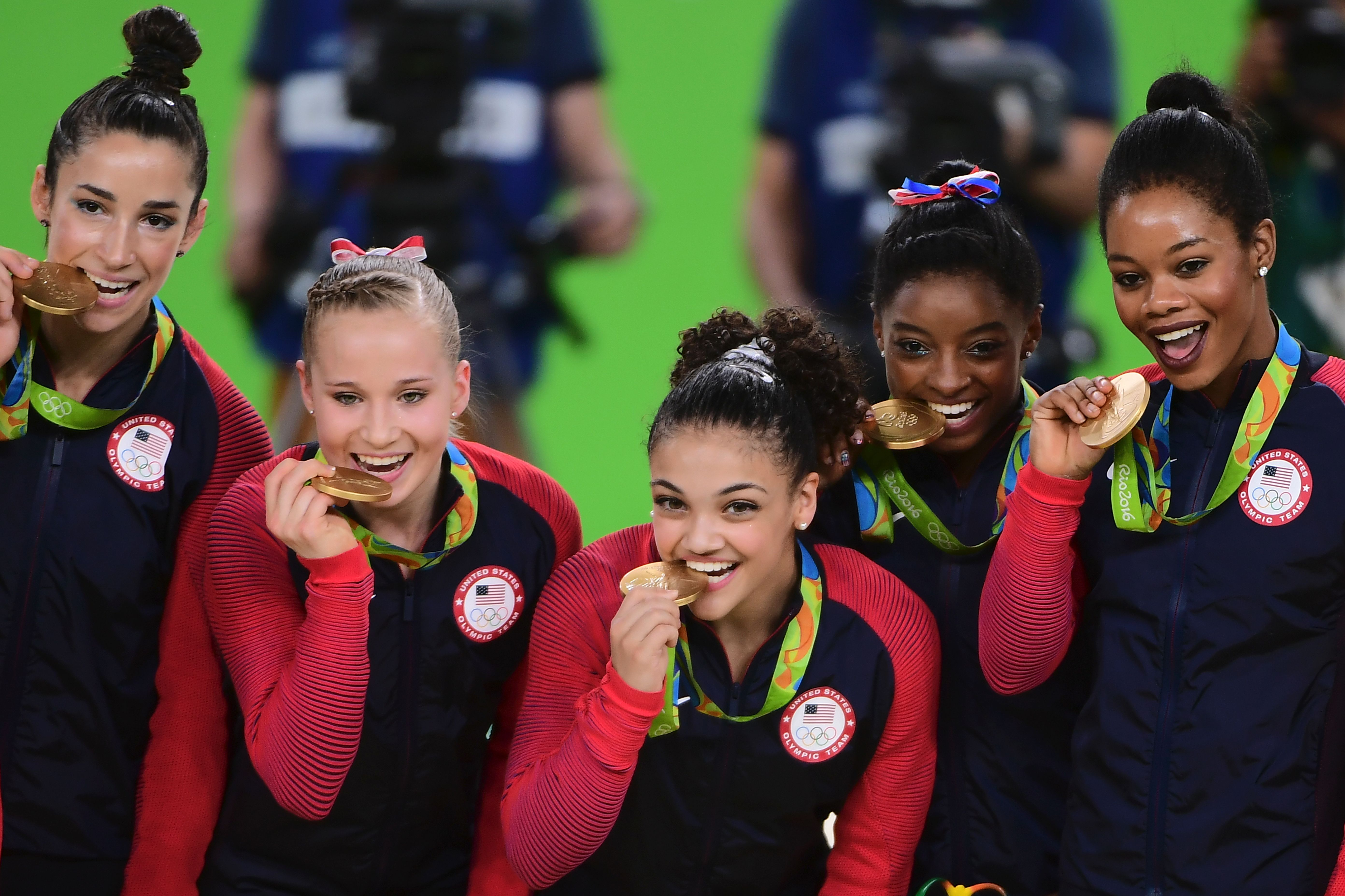 US gymnasts Alexandra Raisman, Madison Kocian, Lauren Hernandez, Simone Biles and Gabrielle Douglas celebrate with their gold medals on the podium during the women's team final Artistic Gymnastics at the Olympic Arena during the Rio 2016 Olympic Games in Rio de Janeiro on August 9, 2016. Photo Credit: EMMANUEL DUNAND/AFP/Getty Images.