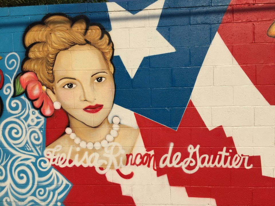 A mural with the Puerto Rican flag as background and a Heroina in the foreground