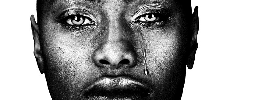 A black woman with dark skin looks at the camera. A tear drips down her cheek.