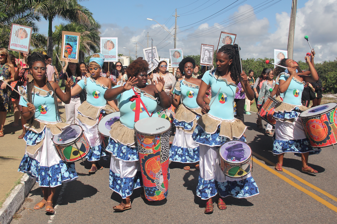 Black women march in the street with African drums