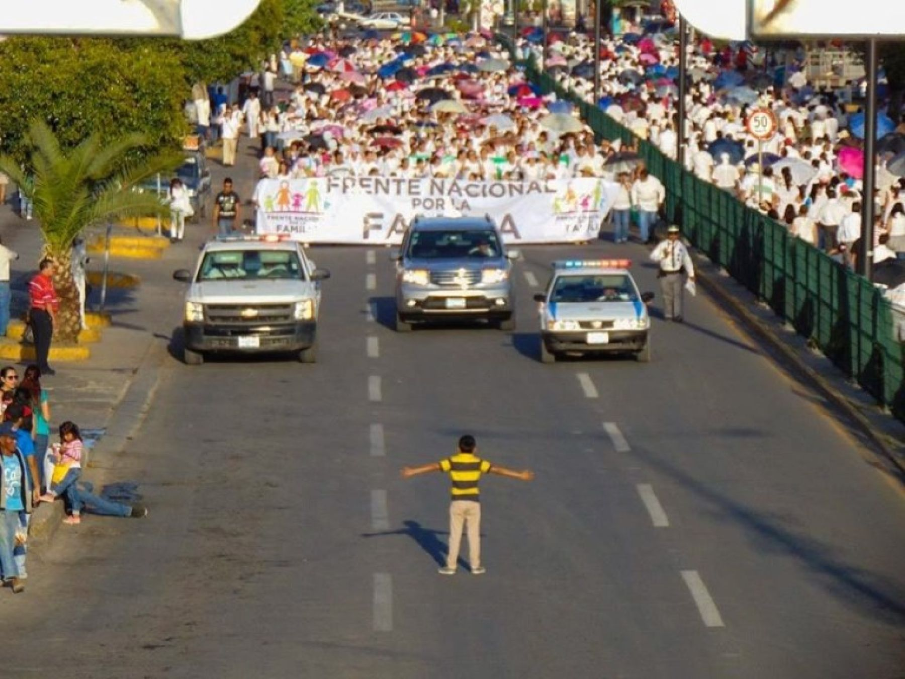 Boy stands in teh street in front of massive demonstration with arms open