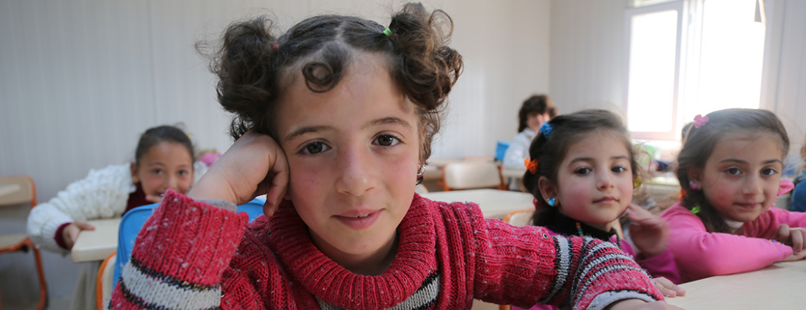 Girls looking into the camera at an education center in Syria