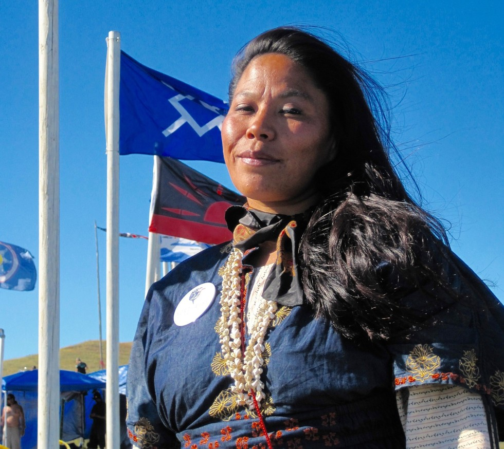 An Indigenous woman proudly stands against a bright blue sky.