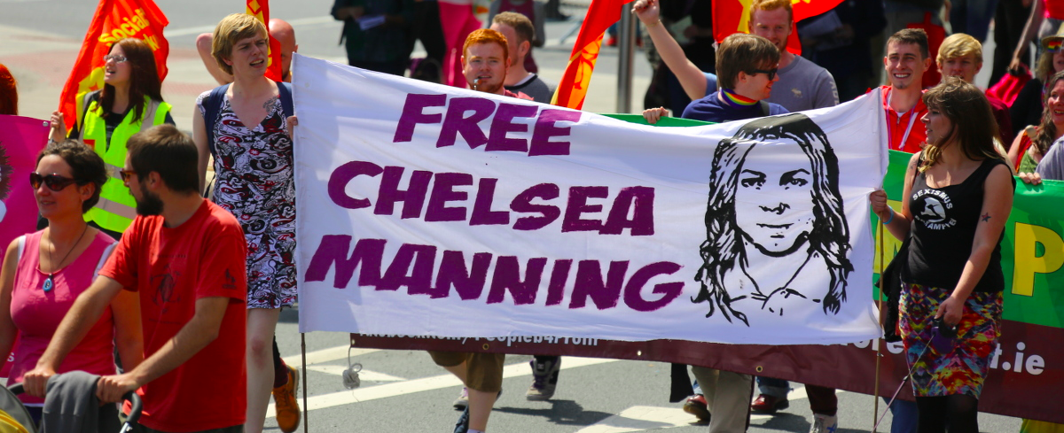 people holding up a free chelsea manning poster