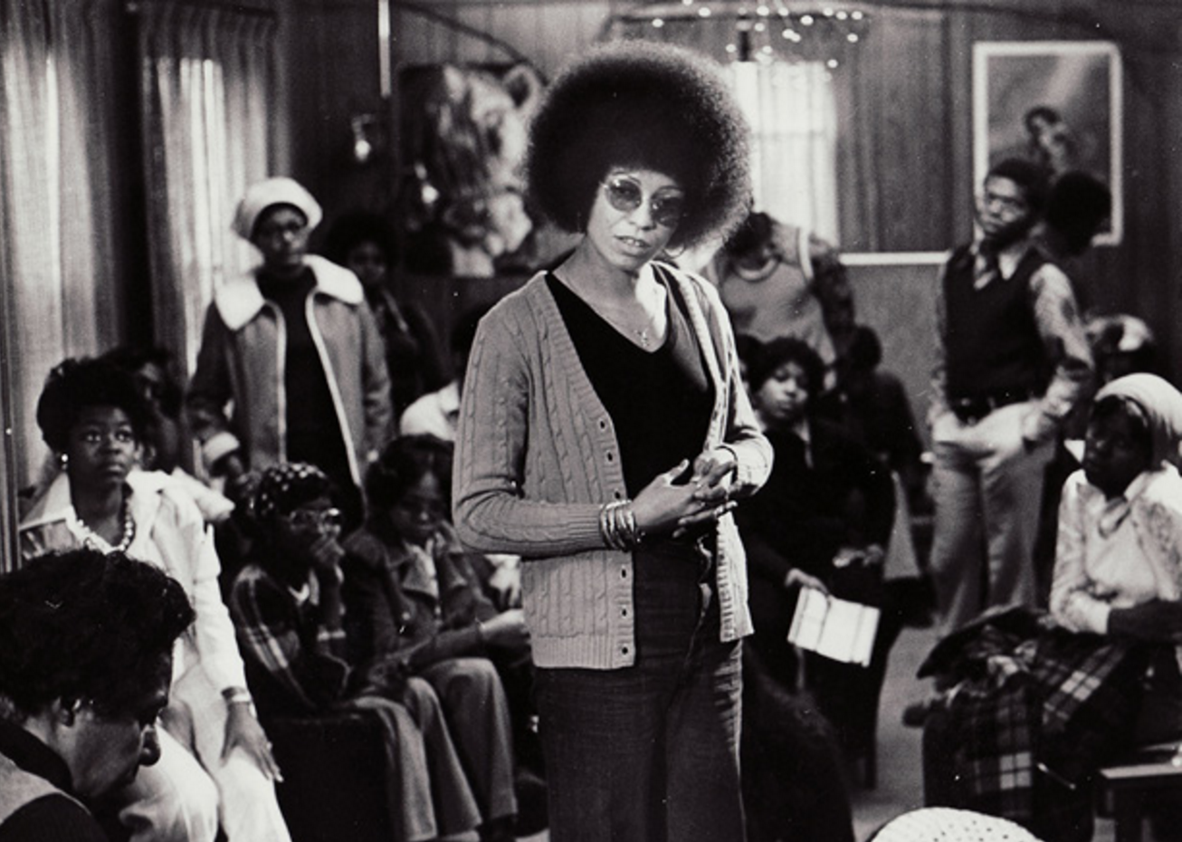 A picture of Angela Davis standing in a room full of people