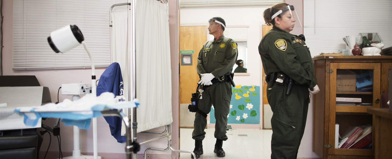 Prison guards escort an inmate held in the Administrative Segregation unit to her appointment with the prison's OB/GYN.