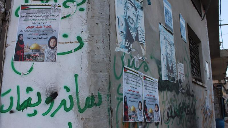 posters on a a building wall in Qarawat Bani Zeid depict Fatima Hjeiji