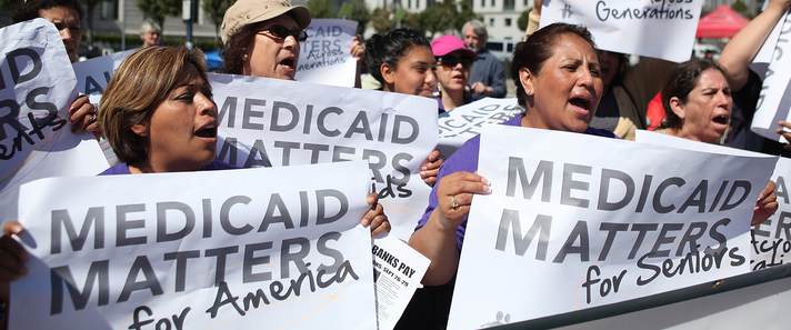 "A group of brown women hold signs saying ""Medicaid matters"" at a protest."