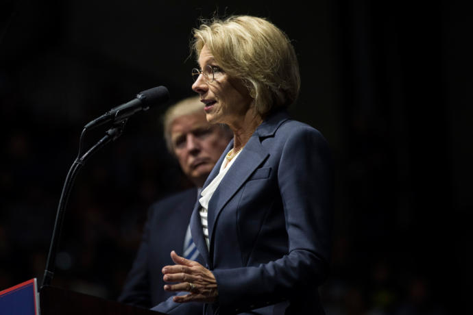 Betsy Devos stands at a mic with Donald Trump behind her.