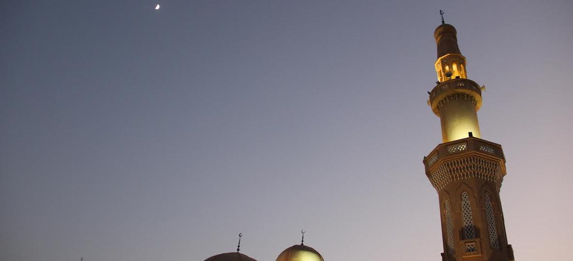The minaret of a mosque is lit up against a night sky.