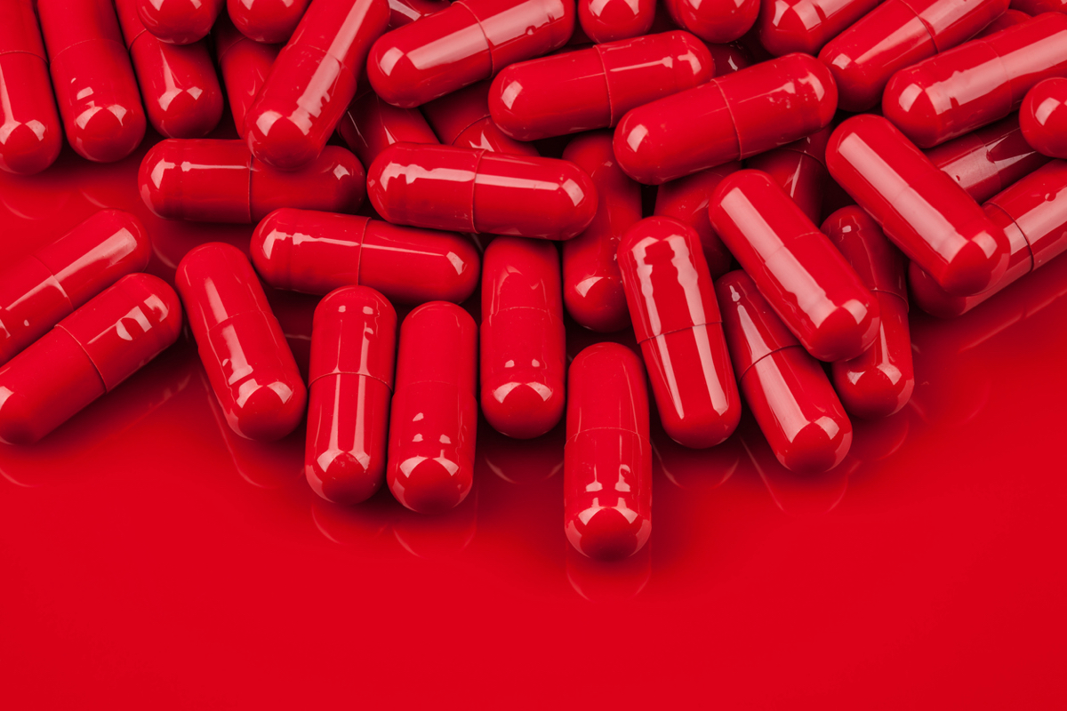 Macro photo of pile of red capsule pills on same color surface with copy space