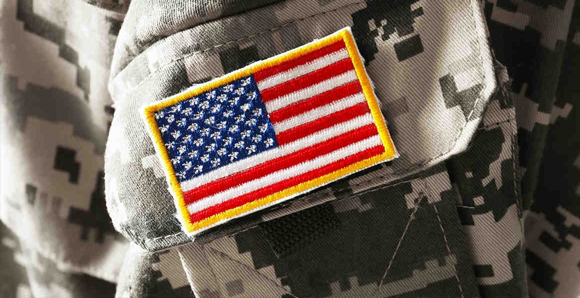 A photo of the U.S. flag on a camouflage uniform.