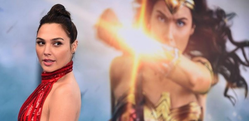 Actress Gal Gadot stands in front of a Wonder Woman banner.
