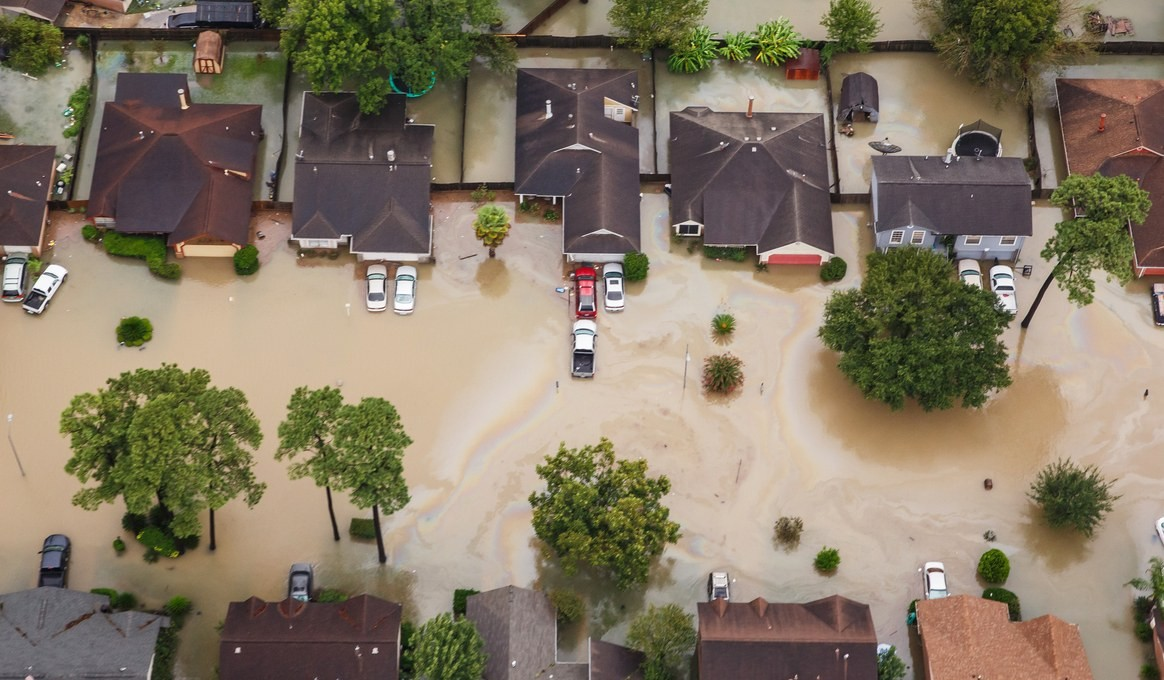 An aerial view of a street with homes hit by Hurricane Harvey