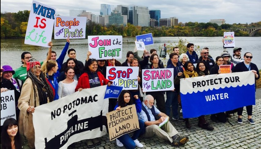 A group of activists hold signs near the potomac river protesting a proposed pipeline.