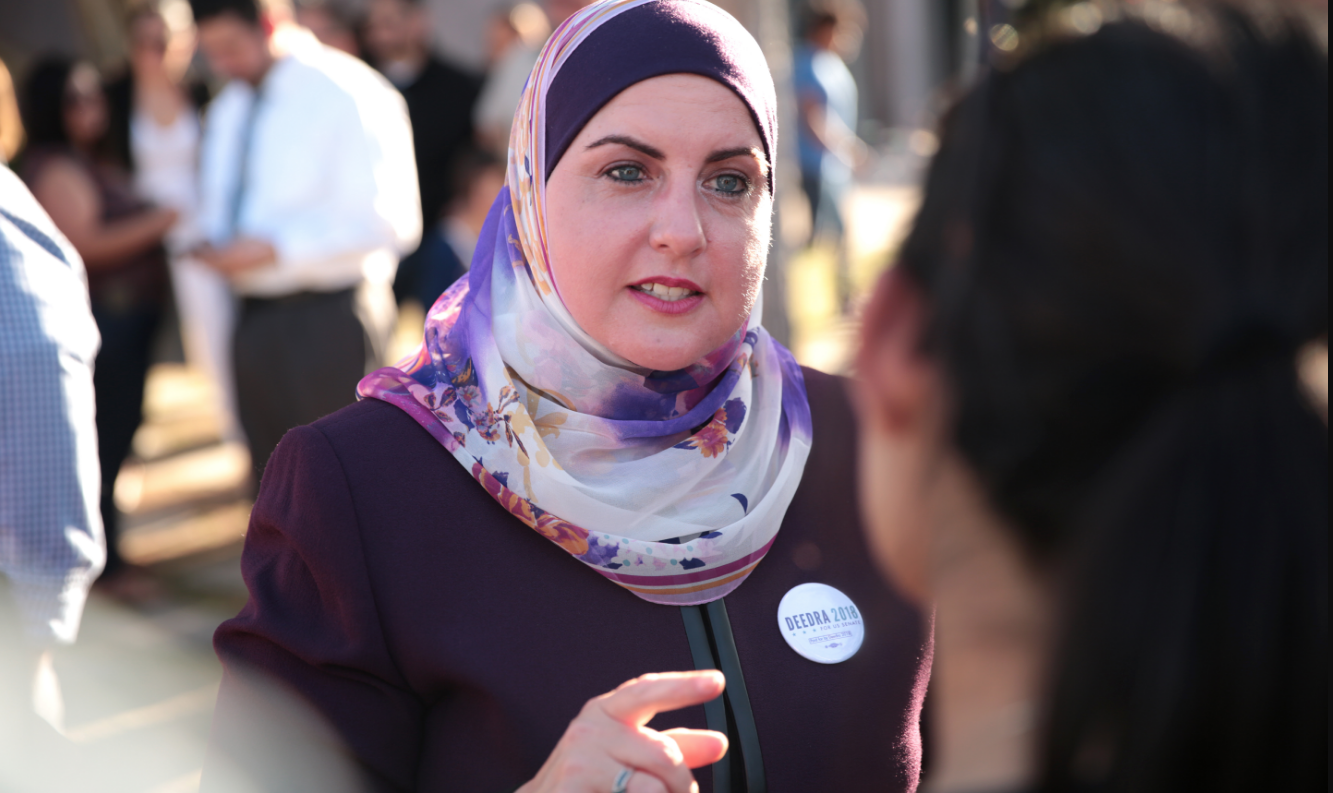A woman with a headscarf, Deedra Abboud, speaks to constiuents.
