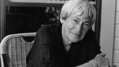 A headshot of Ursula Le Guin smiling into the camera.