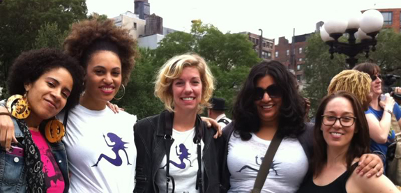 The crew wearing Feministing t shirts smiling at a protest
