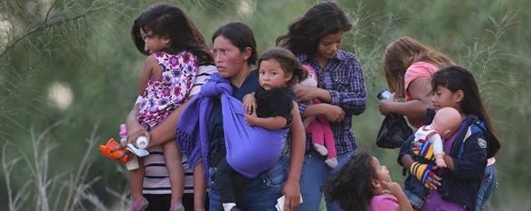 A group of Central American women stand on the side of the road, holding babies.