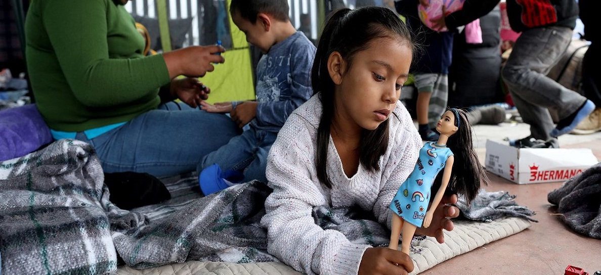Young Latina girl sits in a tent, playing with a doll.