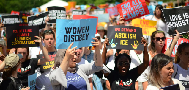 "Image of protesters holding signs saying ""abolish ice""."