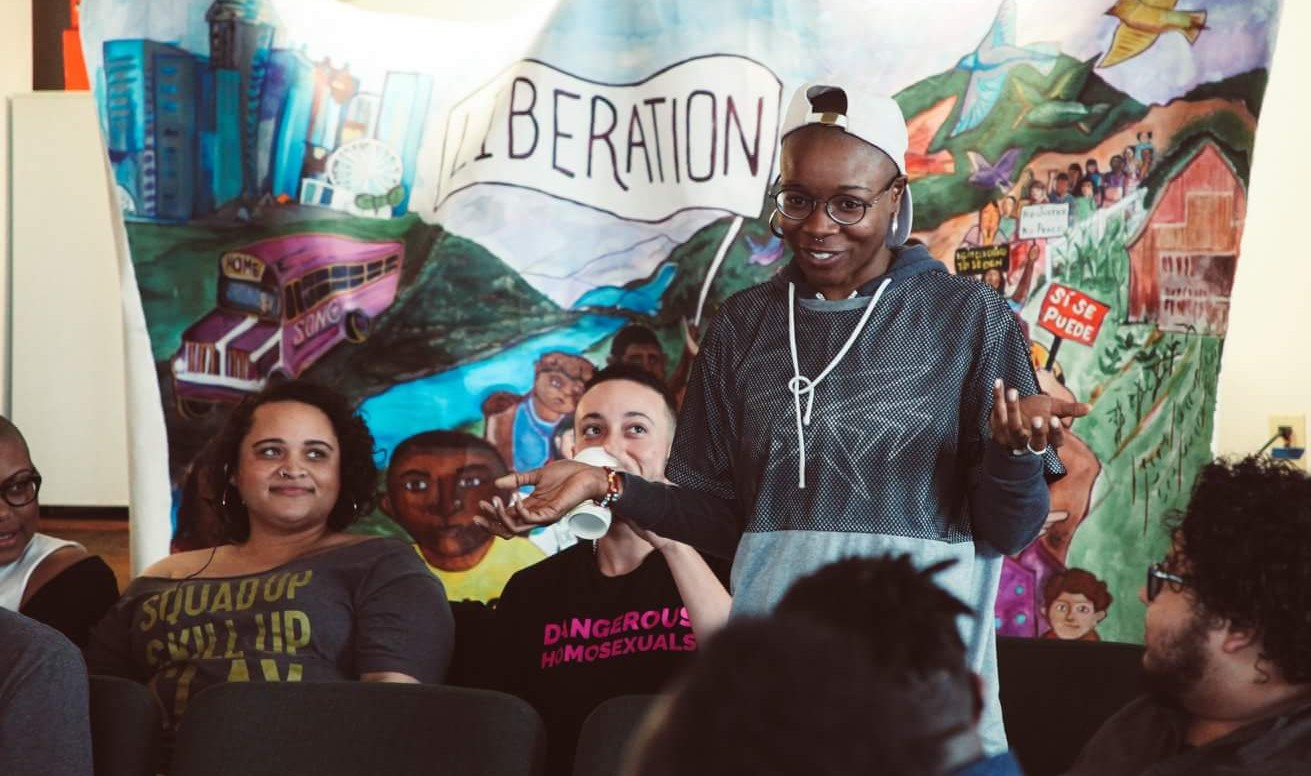 "glo Merriweather speaks in front of a group of people that are sitting down. Behind them are other black and brown folks and a mural that says ""liberation"""