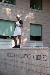 glo Merriweather standing on top of a stone wall that says Mecklenburg County Courthouse