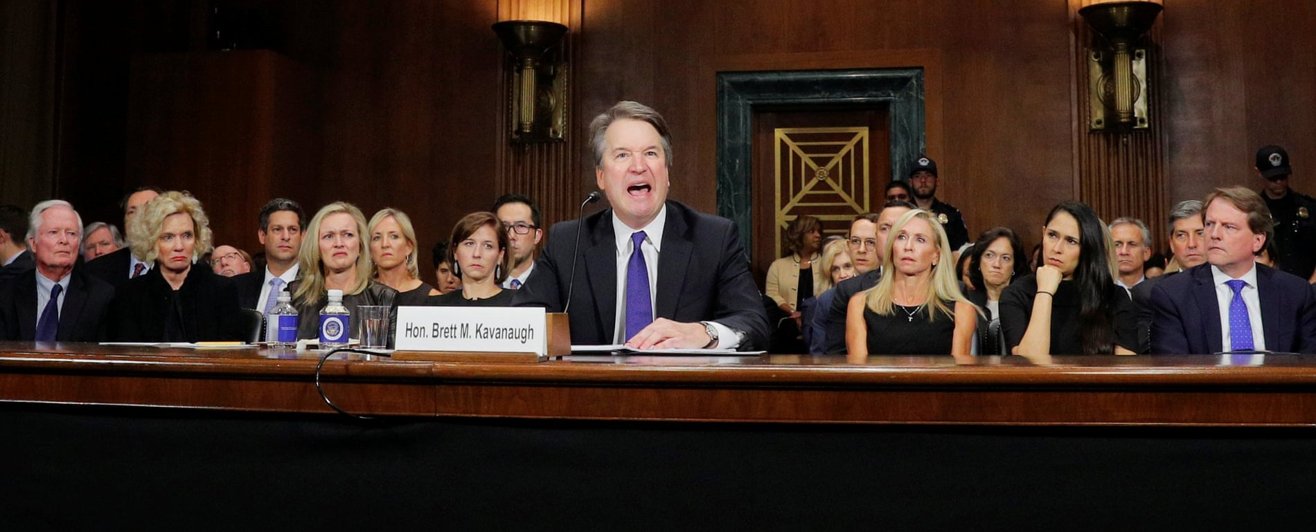 Kavanaugh looking angry while scowling women look on