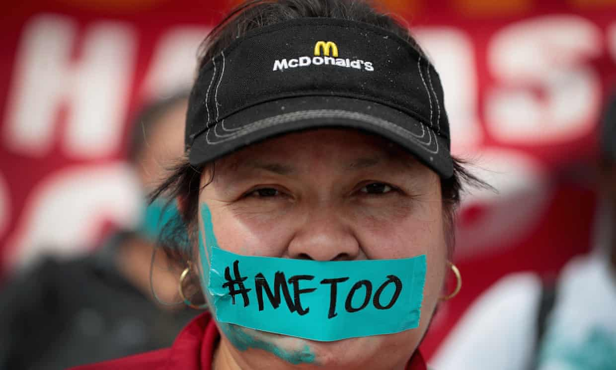 A woman participating in yesterday's McDonald's strike wears a baseball hat looks directly at the camera. There is a piece of blue tape over her mouth that says #MeToo. She has a blue handprint painted on the left side of her face.