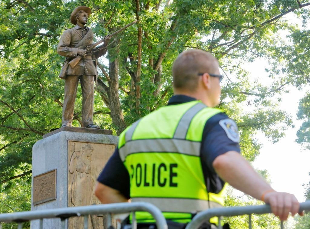 "picture of a white police officer in a bright green vest that says ""police"" on the back standing in front of a metal barricade, facing away from the camera. Behind him is the Silent Sam statue at the University of North Carolina Chapel Hill campus"